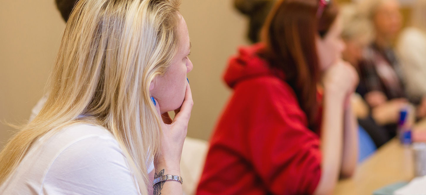 Women in a training room listening to a coercive control workshop